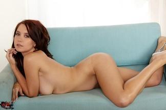 Chrissy Marie a cuatro patas sobre un sofá azul, foto 2